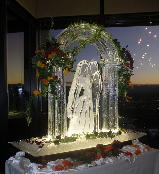 Bride and Groom under 3-d Arch Ice Sculpture with fall flowers
