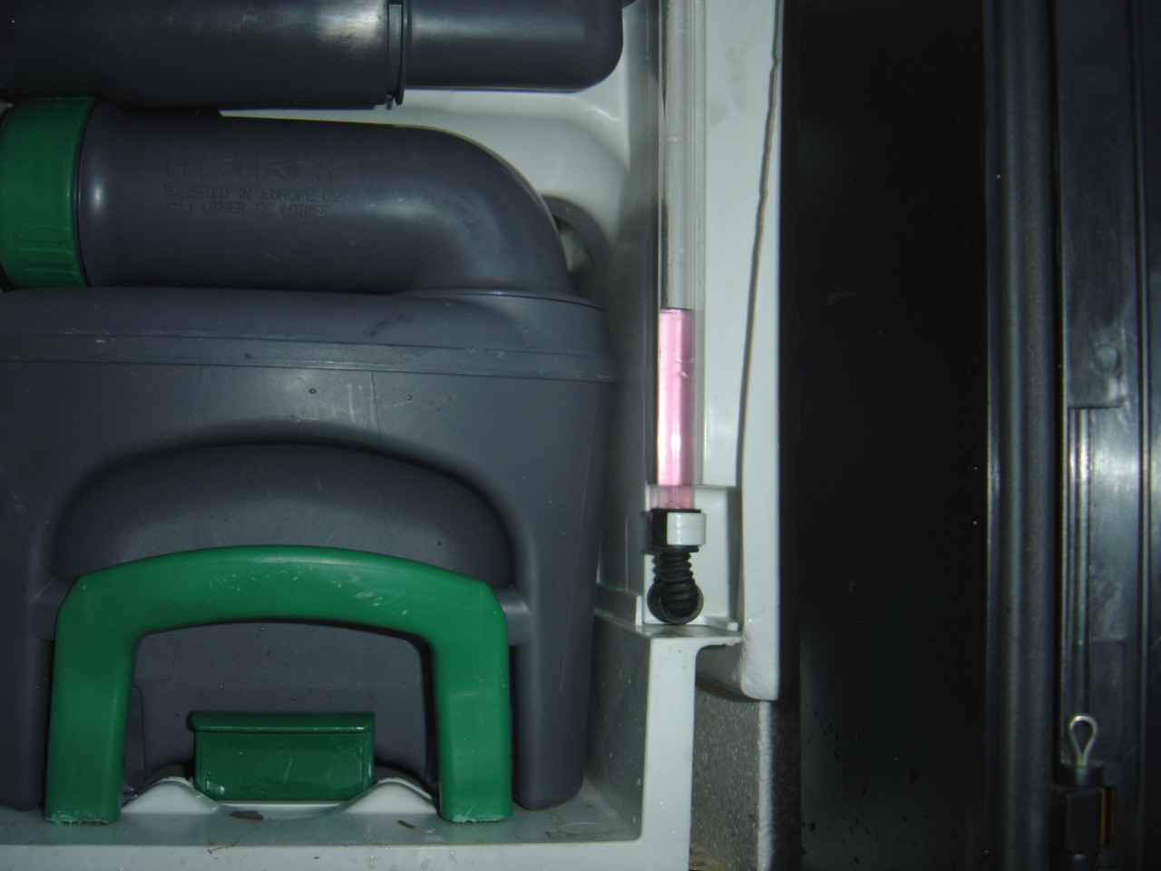 Unlock and open the cassette toilet door and locate the clear plastic sight tube for your freshwater supply to the toilet (seen on the right). As shown here the toilet fresh water tank should have antifreeze in it. This has to be drained out.