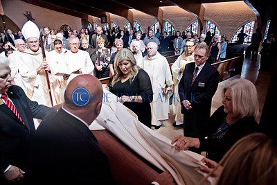 Family members of Deacon David Obergfell help place the funeral pall on top of Deacon Obergfell's casket at the beginning of the Mass of Christian Burial August 3 at St. Pius X Catholic Church.