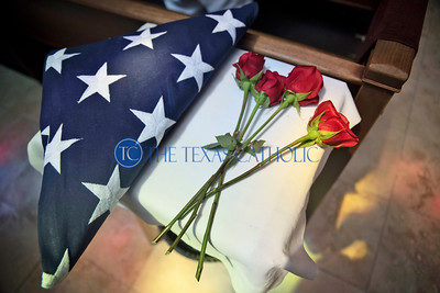 Roses and an American flag are set aside before being handed to the family of Deacon David Oberfgell at the end of the Mass of Christian Burial August 3 at St. Pius X Catholic Church.
