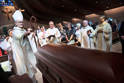 Auxiliary Bishop Greg Kelly begins the Mass of Christian Burial for Deacon David Obergfell by sprinkling holy water on the casket August 3 at St. Pius X Catholic Church.
