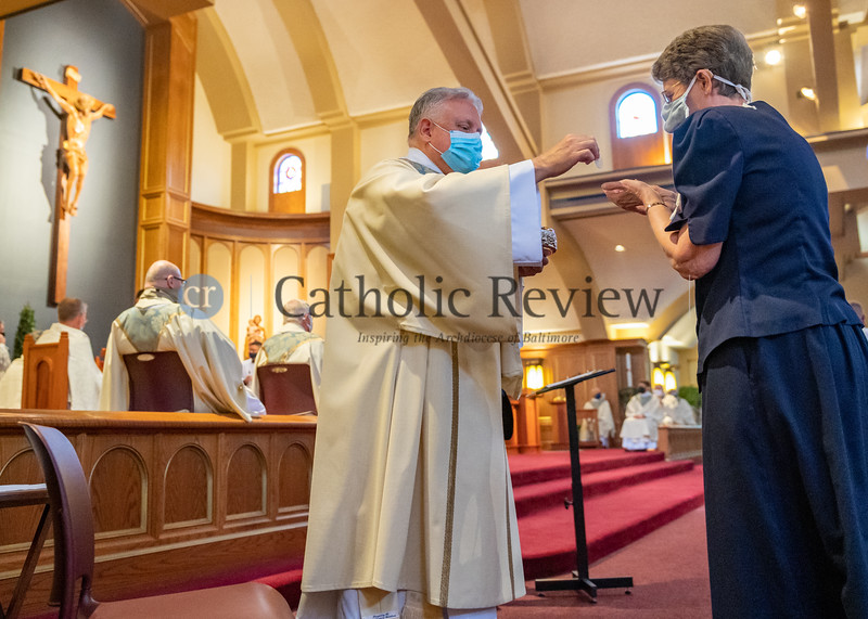 Deacon Scott Kady distributes Communion during his ordination Mass to the diaconate August 8, 2020 at St. Ignatius Church in Hickory. (Kevin J. Parks/CR Staff)