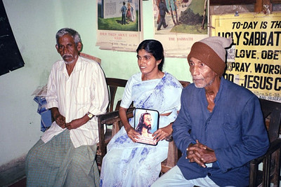 On the right is Mr. Meshak (deaf) who for many years worked to share his faith with other deaf in the Thanjavur area of India. He is shown here sitting with deaf friends in his living room in 2002 where you can see visual aid on the wall that he used to help share his faith.  In 2002 Brother Meshak saw a dream come true, a full time pastor for the deaf in his area and a new church built just for deaf.  Though extremely weak, with help Meshak was able to cut the ribbon opening the first church ever built just for the deaf in the SDA church.  Meshak died shortly after.  Sathiyamoorthy says that when he came to Thanjavur area in 1998 to begin a ministry to deaf, he did not really know what to do, but Meshak helped him, and soon there was a baptism of 18 deaf people.