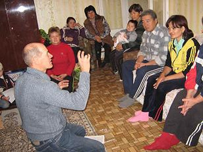 Pavil, kneeling, is leading out in teaching with a group of deaf peoples in Kyrgystan.  Pavil is one of the key founders of the deaf church in Kyrgystan.