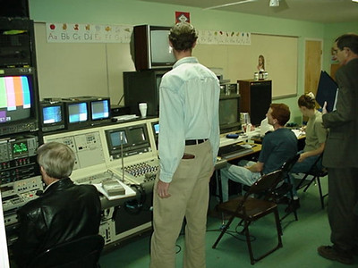 Jim Doss, the 'sound man' watching as his brother, Chip Doss, plays back what was just recorded.  On the right (standing), Pastor Trexler watches to see how it all looks on video.  All the equipment, the video set and lighting had to brought into a gym and classroom for this large project.  We guess that this is one of the largest Bible Study video projects ever done in sign language by a deaf presenter.