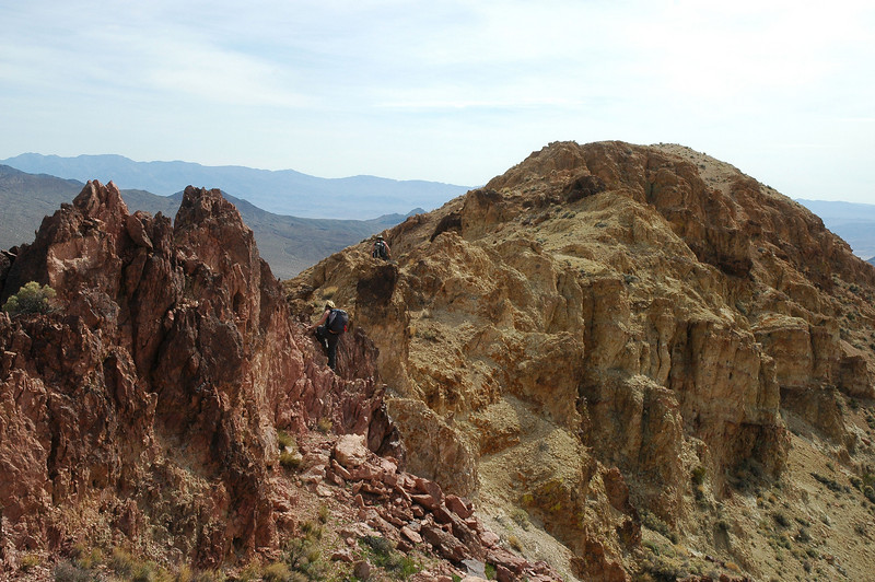 Sooz climbing over the red rocks. Salsberry Peak can barley be seen in this photo.