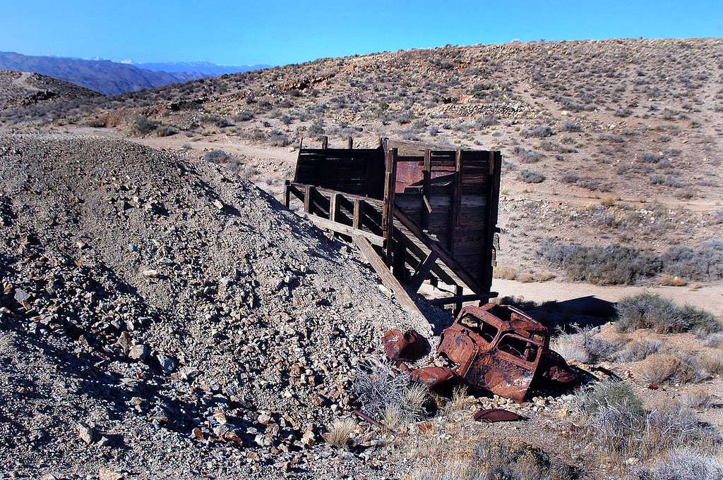 A ore bin and rusty car full of bullet holes. These are the first signs of mining I came upon in the Skidoo area.