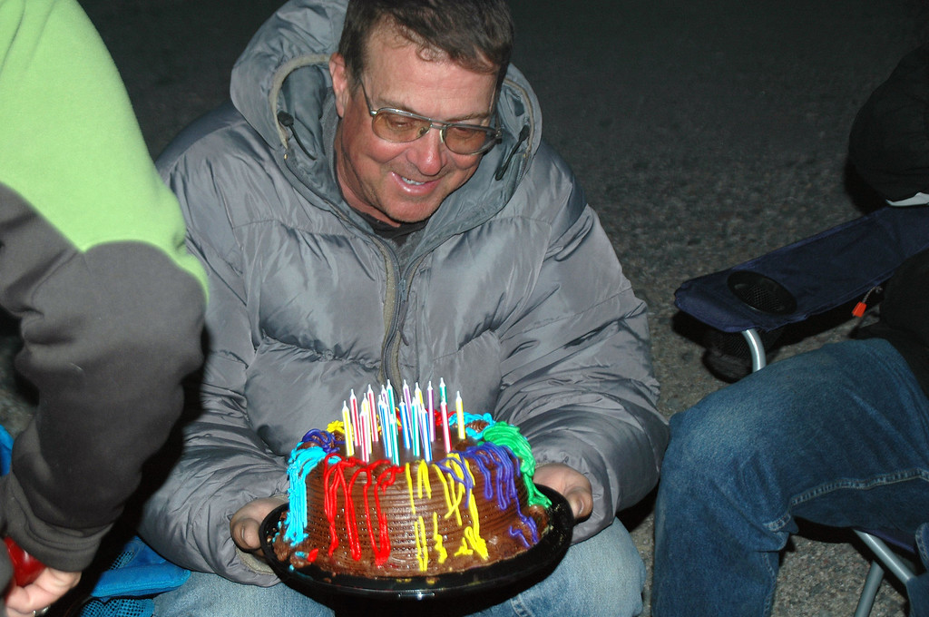 Tom G with the cake. It was to windy to get all the candles lit, but we managed to get one going so he could make a wish.