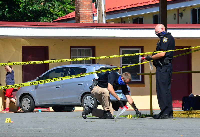 Det. Sgt. Greg Eaton, of the Brattleboro Police Department, gathers evidence during a suspicious death investigation at the EconoLodge, on Canal Street in Brattleboro, Vt., on Friday, July 31, 2020. Kristopher Radder, Brattleboro Reformer via AP