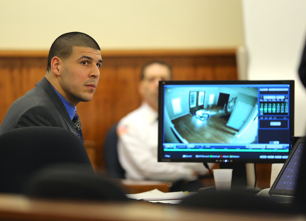 . Former New England Patriots football player Aaron Hernandez looks up as his defense attorney, James Sultan shows a video of Hernandez\'s home as he emerged from the basement, during closing arguments in his trial in Fall River, Mass., Tuesday, April 7, 2015.  Hernandez is accused of killing Odin Lloyd in June 2013.  (AP Photo/The Boston Globe, John Tlumacki, Pool)