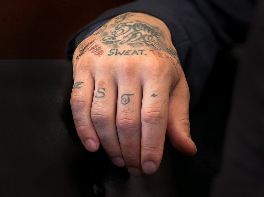 . Tattoos cover the right hand of former New England Patriots football player Aaron Hernandez, as he attends a pre-trial hearing at Suffolk Superior Court in Boston, on Tuesday, Oct. 13, 2015. Judge Jeffrey Locke agreed to postpone the double murder trial of Hernandez while prosecutors try to get their hands on evidence now held by a law firm that previously represented him. Hernandez is accused in the 2012 killings of two Boston men.  He was convicted this year in the June 2013 killing of Odin Lloyd. (David L Ryan/The Boston Globe via AP, Pool)