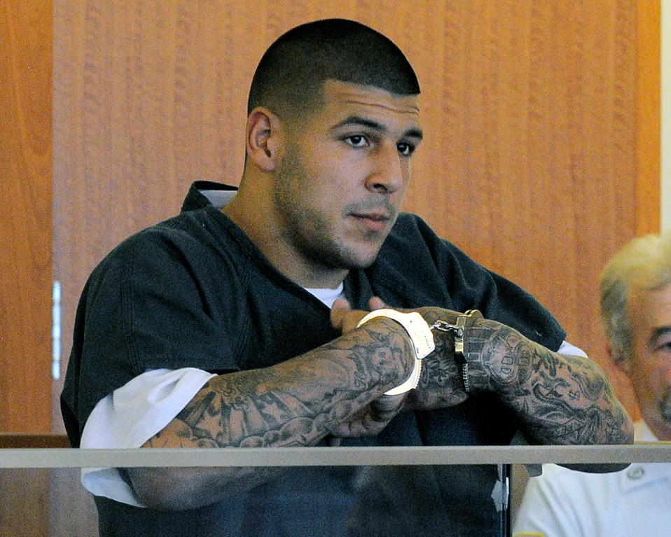 . FILE - In this June 27, 2013 file photo, former New England Patriots football standout Aaron Hernandez stands during a bail hearing in Superior Court in Fall River, Mass., charged with killing Odin Lloyd. Hernandez is scheduled to be arraigned May 28, 2014, on two unrelated murder charges in the 2012 shooting deaths of Daniel de Abreu and Safiro Furtado in Boston. Prosecutors are also seeking assistance from tattoo artists who may have inked Hernandez\'s right arm between February 2012 and June 2013. The tattoo artists are considered witnesses, not suspects. (AP Photo/Boston Herald, Ted Fitzgerald, Pool, File)