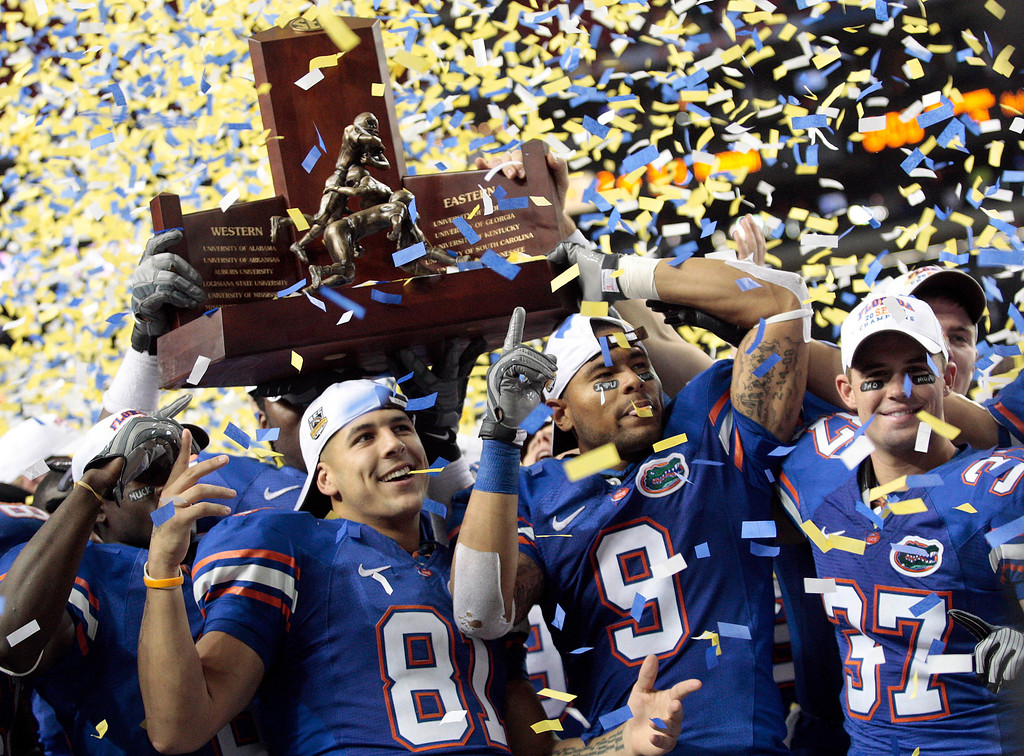 . FILE - In this Saturday, Dec. 6, 2008, file photo, the Florida Gators, from left, Aaron Hernandez (81), Louis Murphy (9) and Butch Rowley (37) celebrate after receiving the SEC Championship Trophy following a 31-20 win over top-ranked Alabama in the Southeastern Conference Championship NCAA college football game at the Georgia Dome in Atlanta. Hernandez, who was serving a life sentence for a murder conviction and just days ago was acquitted of a double murder, died after hanging himself in his prison cell Wednesday, April 19, 2017, Massachusetts prisons officials said. (AP Photo/Dave Martin, File)