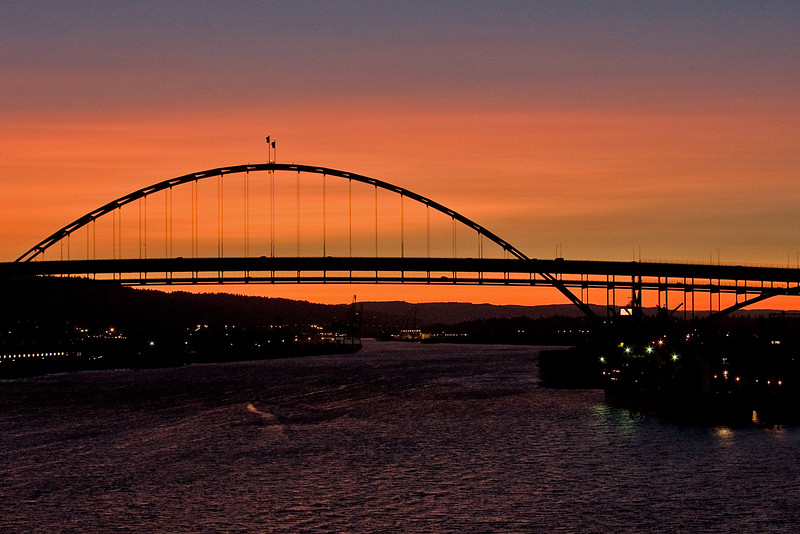 6/29/09: Portland has 8 bridges that cross its 2 rivers. In this photo, I am stuck on the Broadway bridge waiting for a grain ship to pass under.  Good thing I had my camera.  I got out of the car and took a photo of one of the other bridges, the Fremont Bridge, with the sunset behind it. -Deb