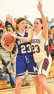 KYLE MENNIG - ONEIDA DAILY DISPATCH Madison's Courtney Cochran, left, looks to move the ball up the court after grabbing a rebound as Stockbridge Valley's Adrianna Cox defends during their game in Munnsville on Saturday, Dec. 17, 2016.