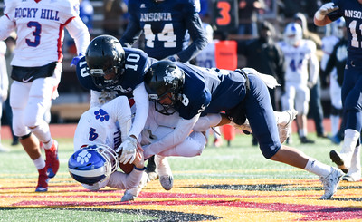 121016 Wesley Bunnell | Staff  Ansonia defeated Rocky Hill 28-21 in the Class S Football Championship Saturday at Veteran's Stadium in New Britain. Ansonia's Brent Washington (10) and Justin Lopez (11) tackle Rocky Hill QB Daniel Cavallaro (4).