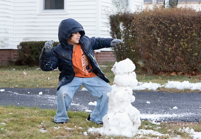 121216  Wesley Bunnell | Staff  Joshua Ridl Jr. , age 7, takes a break from building his snowman with the remnants of Monday mornings storm to have a snowball fight with a friend.
