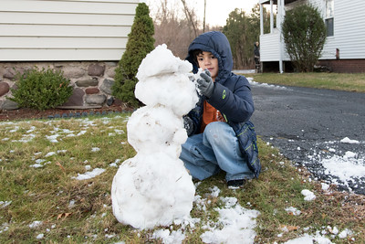 121216  Wesley Bunnell | Staff  Joshua Ridl Jr. , age 7, builds a snowman Monday afternoon with the remnants of Monday mornings storm.