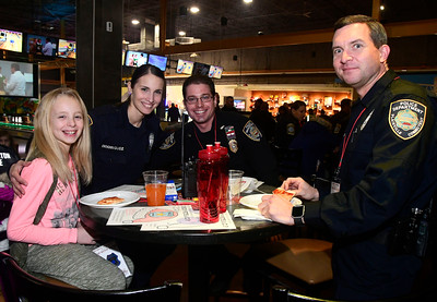 12/13/2016 Mike Orazzi | Staff Jessica Rogers sits with Plainville Police Officers Evelyn Rodriguez, David Slater and David Posadas during the REACH Foundation's annual Shop With a Cop event held at Crystal Bees in Southington Tuesday evening.