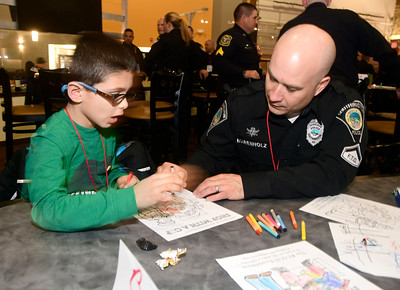 12/13/2016 Mike Orazzi | Staff Joe Amarante colors with Southington officer John Marenholz during the Shop with a Cop event held at Crystal Bees in Southington Tuesday evening.