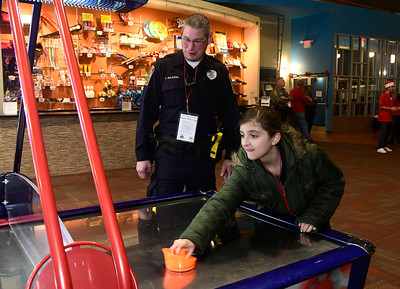 12/13/2016 Mike Orazzi | Staff Bristol Police Officer Patrick Krajewski and Paige Morales during the REACH Foundation's annual Shop With a Cop event held at Crystal Bees in Southington Tuesday evening.