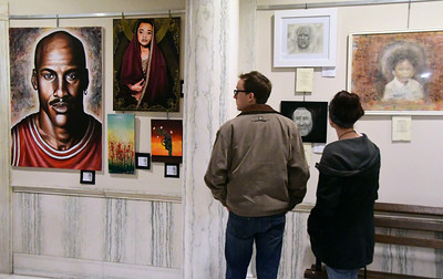 12/14/2016 Mike Orazzi | Staff Chris Dudanowicz and Sarah Wiegert admire artwork on display during the Art in the Heart of the City Mayor's Invitational Opening Reception at city hall Wednesday.