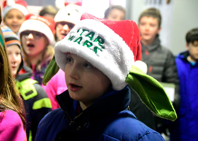 12/15/2016 Mike Orazzi | Staff South Side School's Community Club student Darrek Griffith sings Christmas carols while delivering coffee and doughnuts to staff at the police and fire departments, and the post office in Bristol Thursday morning.