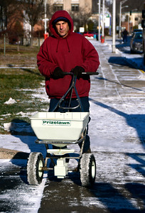 12/15/2016 Mike Orazzi | Staff Mark Bentivengo applies ice melt along North Main Street in Bristol in front of the police station Thursday morning.