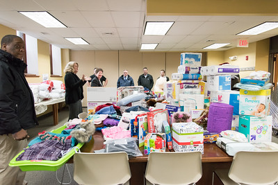 121916  Wesley Bunnell | Staff  Papa's Chrysler Dodge Jeep delivered a stuffed van full of toys and other necessities to the Prudence Crandall Center on Monday afternoon. Prudence Crandall Center Director of Development Carolyn Jasper, second from the left, addresses the group after they finished carrying the donated items into the center.