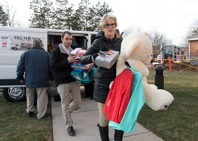 121916  Wesley Bunnell | Staff  Papa's Chrysler Dodge Jeep delivered a stuffed van full of toys and other necessities to the Prudence Crandall Center on Monday afternoon.  Service Advisor Jordan McMahon and owner of Papa's Lisa Papa-Thiesfeldt carry toys and clothes into the center.