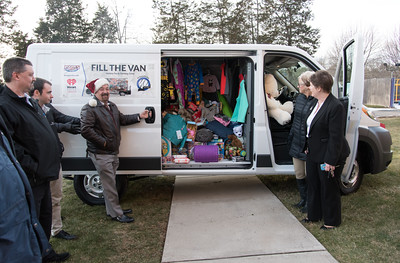 121916  Wesley Bunnell | Staff  Papa's Chrysler Dodge Jeep delivered a stuffed van full of toys and other necessities to the Prudence Crandall Center on Monday afternoon.  Papa's Director of Marketing A.J. Maida slides open the van door with Carolyn Jasper and Barbara Damon from the Prudence Crandall Center on the right.