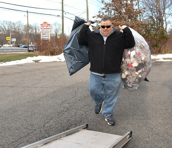122116  Wesley Bunnell | Staff  PMG Insurance & Financial Services delivered toys to the Connecticut Children's Medical Center on Wednesday afternoon as part of their holiday toy drive.  President of PMG Insurance & Financial Services , Bob Sisti, carries bags of soft animal toys onto the loading ramp of a sixteen foot box truck used for delivery.