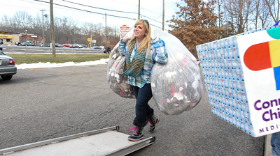 122116  Wesley Bunnell | Staff  PMG Insurance & Financial Services delivered toys to the Connecticut Children's Medical Center on Wednesday afternoon as part of their holiday toy drive.  Tracy Sisti, carries bags of soft animal toys onto the loading ramp of a sixteen foot box truck used for delivery.