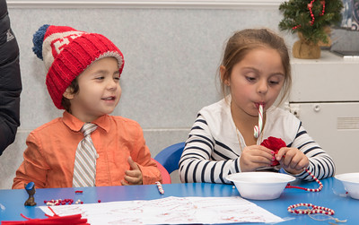120216  Wesley Bunnell | Staff  Hunter Kehn, age 3, keeps an eye on his sister Brenna Kehn, age 5, as she eats her candy cane after visiting Santa Claus. Santa's Workshop was held on Friday evening at the Mortensen Community Center in Newington.