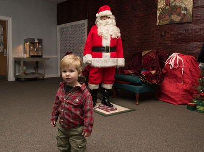 120216  Wesley Bunnell | Staff  Cullen O'Neil, age 20 months, is interested in the camera before sitting on Santa's lap during Santa's Workshop held on Friday evening at the Mortensen Community Center in Newington.