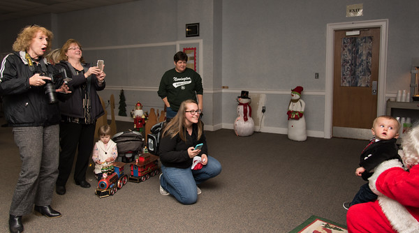 120216  Wesley Bunnell | Staff  Cole Ball, age 10 months, looks back at Santa as a plethora of photographers prepare to take his photo during Santa's Workshop on Friday evening at the Mortensen Community Center in Newington. Kneeling is his mother Michelle Ball and standing in the middle is his grandmother Angela Lach.