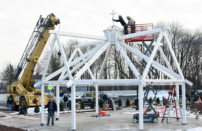 122216  Wesley Bunnell | Staff  A pavilion is being erected with materials and labor donated by Berlin Steel and Manafort Brothers next to St. Paul's in Berlin. Workers affix the cross to the top beam of the pavilion on Thursday afternoon.