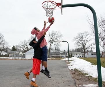 122616  Wesley Bunnell | Staff  Friends spent their Monday off from school playing basketball at DiLoreto Elementary & Middle School's basketball court.  Amran Morrison, age 14, goes up for a layup against Ricshone Wallace, age 11.