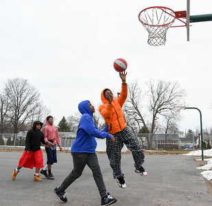 122616  Wesley Bunnell | Staff  Friends spent their Monday off from school playing basketball at DiLoreto Elementary & Middle School's basketball court. Jakari Wilson, age 13, takes a shot guarded by Rashaad Morrison, age 14,  while friends Ricshone Wallage, age 11, far left and Amran Morrison, age 14, watch.