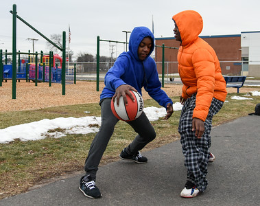 122616  Wesley Bunnell | Staff  Friends spent their Monday off from school playing basketball at DiLoreto Elementary & Middle School's basketball court. Rashaad Morrison, age 14, dribbles against friend Jakari Wilson, age 13.
