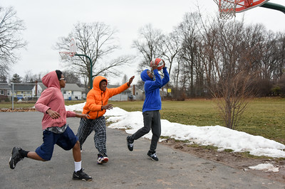 122616  Wesley Bunnell | Staff  Friends spent their Monday off from school playing basketball at DiLoreto Elementary & Middle School's basketball court. From left, Amran Morrison, age 14, and Jakari Wilson, age 13, try to stop Rashaad Morrison, age 14, as he takes a shot.
