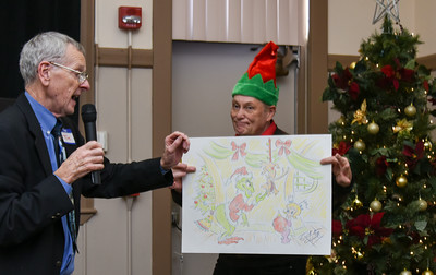 122716  Wesley Bunnell | Staff  The Bristol Historical Society held Winter Wonderland II on Tuesday Dec 27 with kid friend activities and movies.  Tom Dickau, left, pulls a winning raffle number for a Grinch drawing by Cortland Hull.