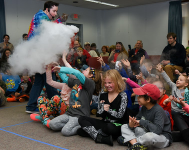 122716  Wesley Bunnell | Staff  Dragons & Dreams by Scientellers held an educational performance at the Berlin-Peck Library on Tuesday Dec 27 for elementary aged children.  Stories about dragons and sorcerers were used to illustrate different science experiments. Scienceteller Eric Dann uses dry ice to substitute for the dragons breath during the story while Michael Olson, age 5 far fight, and Carolyne Niemec, to his left, react.