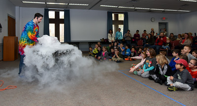 122716  Wesley Bunnell | Staff  Dragons & Dreams by Scientellers held an educational performance at the Berlin-Peck Library on Tuesday Dec 27 for elementary aged children.  Stories about dragons and sorcerers were used to illustrate different science experiments. Scienceteller Eric Dann uses dry ice to substitute for the dragons breath during the story.