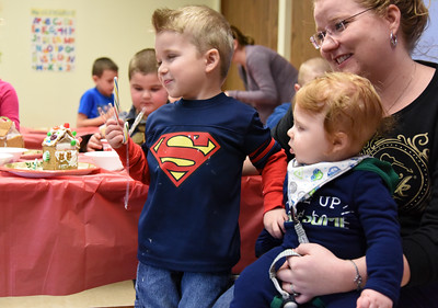 122816  Wesley Bunnell | Staff  The New Britain Children's Museum held a gingerbread house making class on Wednesday Dec 28.  Liam Rafiee, shown left age 3, takes a break to enjoy a candy cane with his mother and 6 month old brother Quinn.