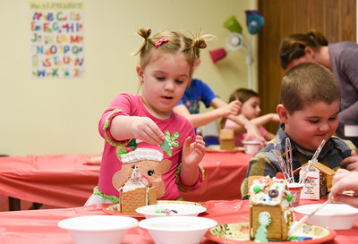 122816  Wesley Bunnell | Staff  The New Britain Children's Museum held a gingerbread house making class on Wednesday Dec 28.  Josie Tiano, age 3, places candy decorations on her house.