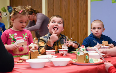 122816  Wesley Bunnell | Staff  The New Britain Children's Museum held a gingerbread house making class on Wednesday Dec 28. Adam Tiano, age 5, jokes with his siblings Josie Tiano, age 3 shown left, and Nathan Tiano, age 7.
