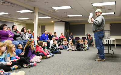 122716  Wesley Bunnell | Staff  Richard Roth of Creature Teachers holds an Umbrella Cockatoo named Zema for the audience at the Plainville Library on Tuesday evening Dec 27. Creature Teachers specializes in environmental and animal education.