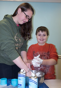 122816  Wesley Bunnell | Staff  Plainville's public library held Magical Mixtures on Wednesday Dec 28 for elementary aged children. Alex Berti, age 8 shown right, makes a snow mixture with shaving cream and powder with the help of his sister Courtney Berti.