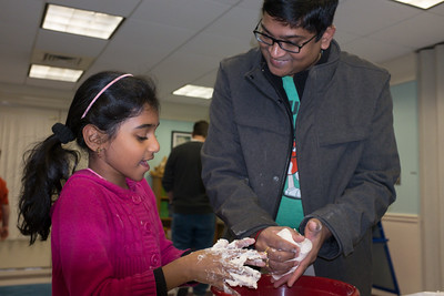 122816  Wesley Bunnell | Staff  Plainville's public library held Magical Mixtures on Wednesday Dec 28 for elementary aged children. Raj Irri, right, helps his daughter's friend Deeksha Anilkumar, age 8, with a home made dough mixture.